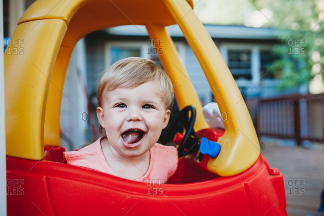Toddler girl sitting in a toy car making a silly face