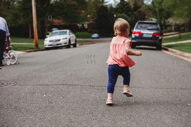 Toddler girl running and playing in a street