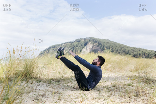 Athletic man sitting down and stretching in the sand