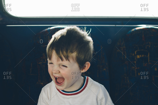 Excited young boy sitting on train beneath window