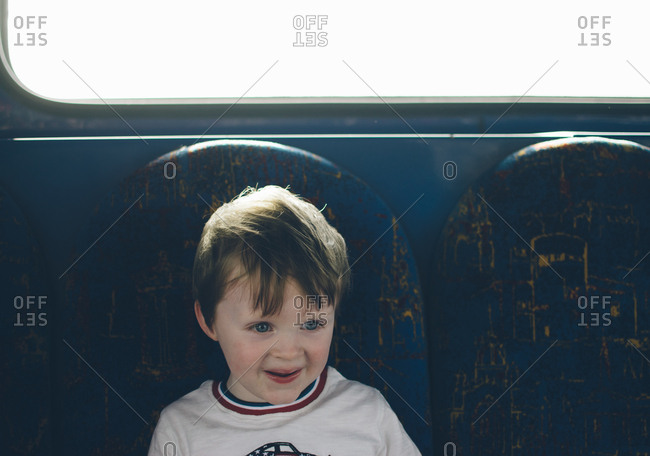 Boy sitting beneath window on train