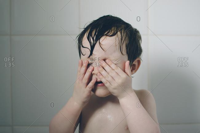 Boy in bathtub covering his eyes