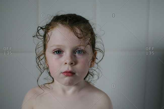 Portrait of young girl with wet curls in bathtub