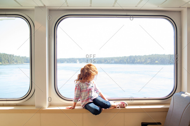 Redhead girl sitting on windowsill looking out on a boat
