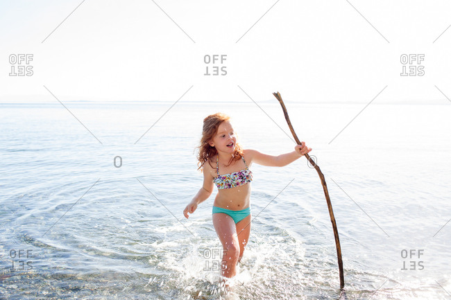 Little girl running with a stick in water
