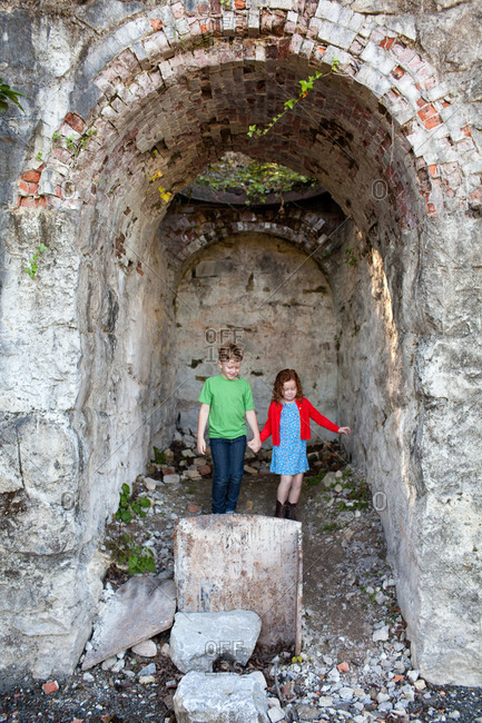 Two children standing underneath arch holding hands