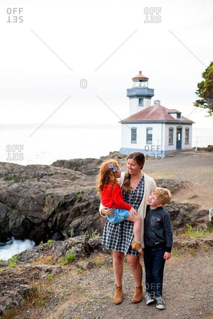 Mother standing by a lighthouse with her children
