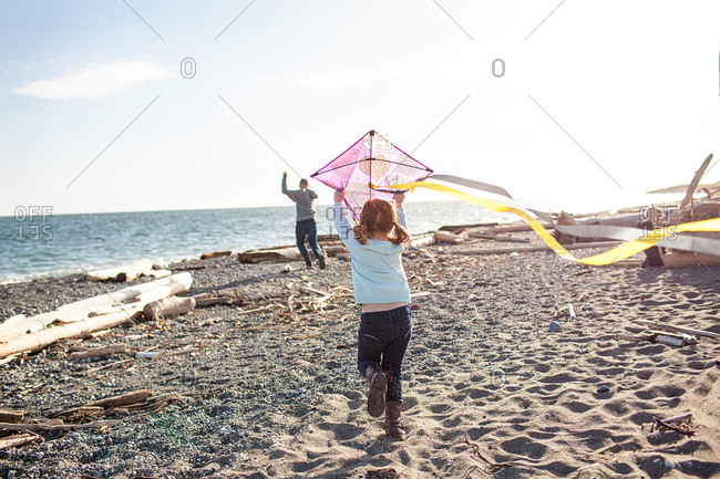 Father helping daughter fly kite on a beach