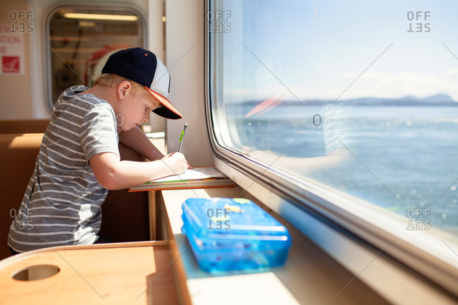 Little boy writing on paper while riding on a ferry