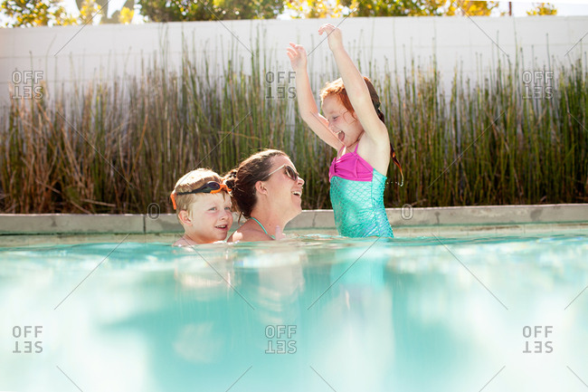 Mother and kids swimming in a pool