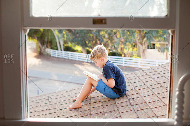 Little boy sitting on a roof reading a book