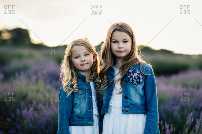 Portrait of two girls standing together in a field of purple lavender flowers