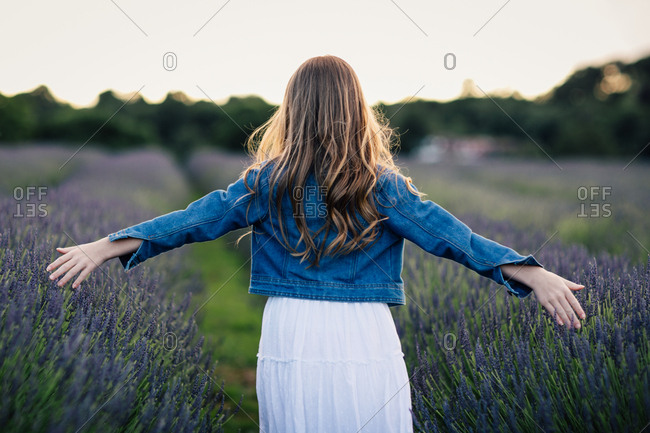 Back view of girl standing with outstretched arms in a field of lavender flowers