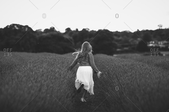 Back view of girl running through a field of lavender flowers