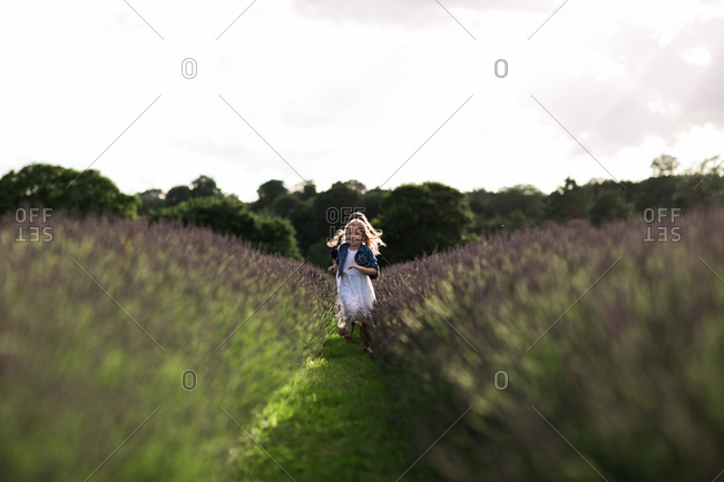 Two girls running through a field of lavender flowers