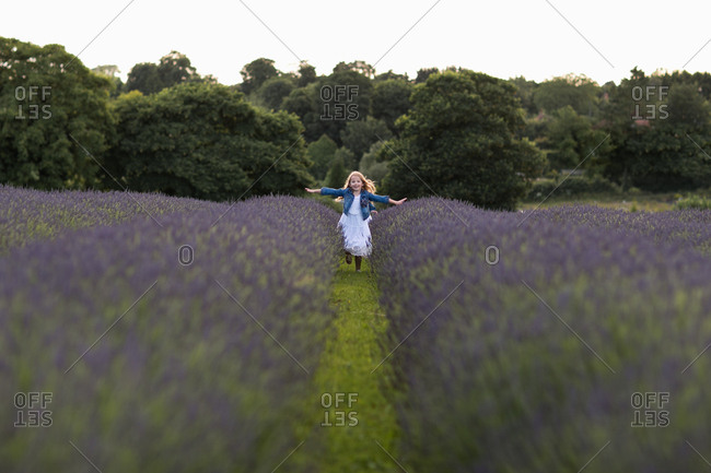 Girl running with outstretched arms through a field of lavender flowers