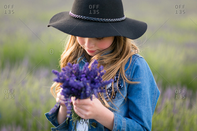 Girl wearing a cowboy hat holding a bunch of freshly picked lavender flowers