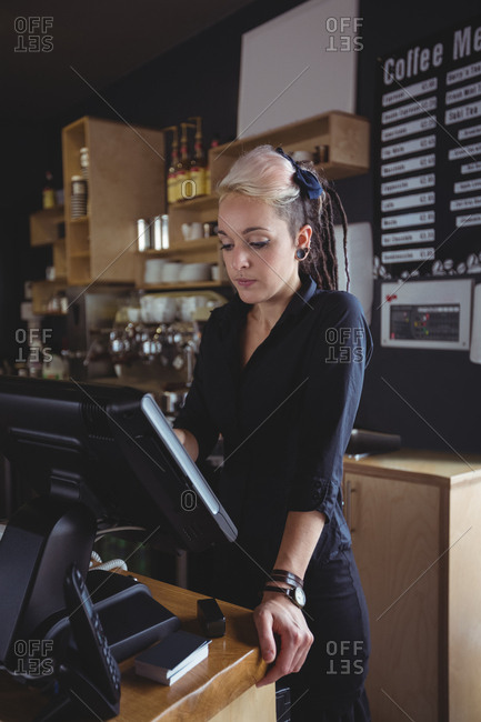 Waitress using cash register at counter
