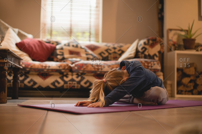 Girl performing yoga in living room