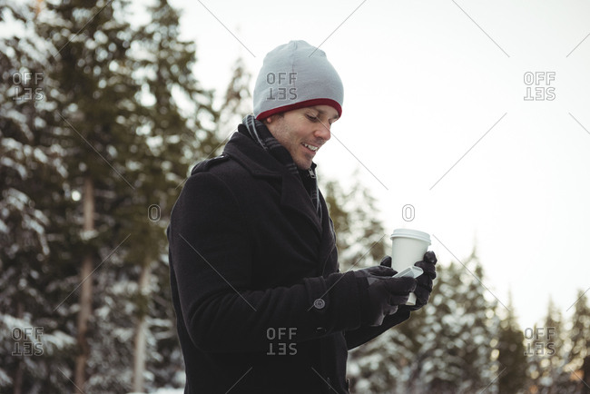 Man in warm clothing using mobile phone
