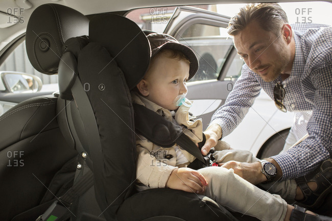 Father fastening son's  seat belt
