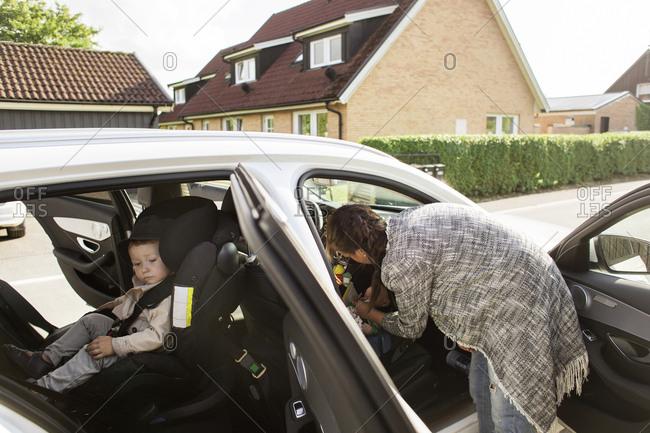 Mother fastening son's seat belt