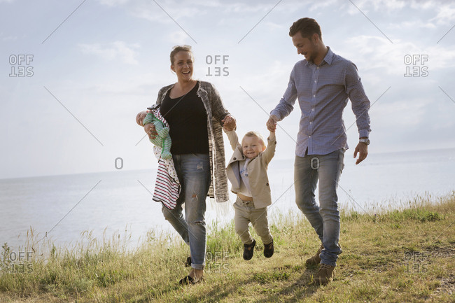 Parents with sons walking by sea