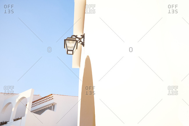Low angle view of traditional forged street lamp on beige house wall, cloudless blue sky and part of adjoining building seen on background