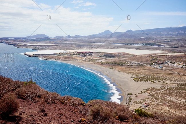 Lovely summer day in nature: deep blue water, empty seashore and high mountains on background, view from hill