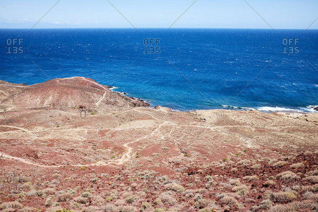 Beauty of wild nature: deep blue water of Atlantic Ocean, cloudless sunny sky and coast with red sand
