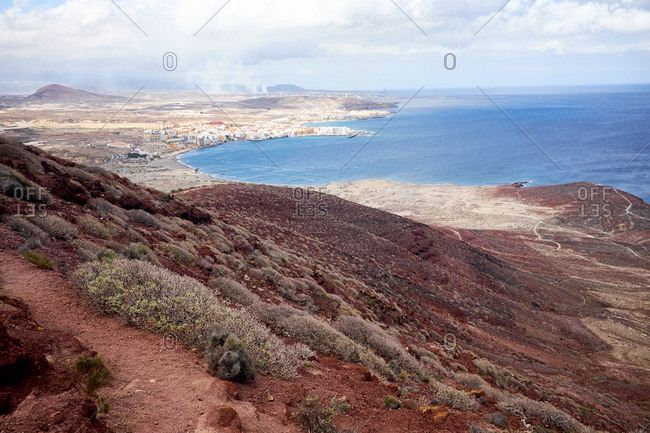 Discovering Tenerife: unforgettable view of pretty coastal town, deep blue water surface of Atlantic Ocean and cloudy sky