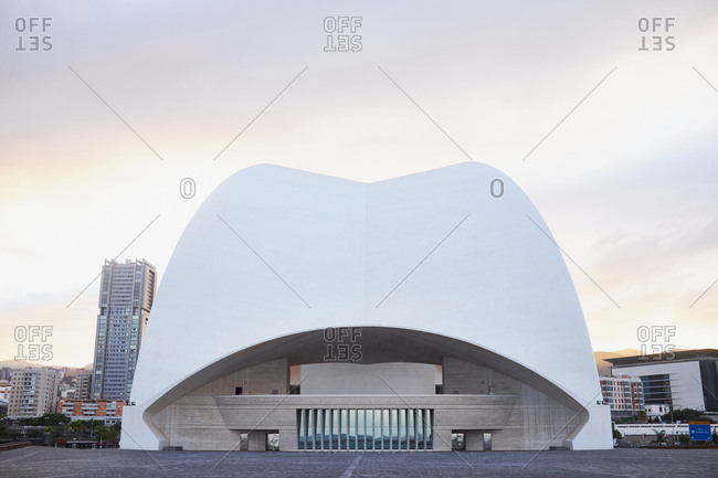 Tenerife, Spain - May 9, 2016: Architectural symbol of Canary Islands: Auditorio de Tenerife against grey sky with flash of sunlight, pervasive atmosphere of peace and quiet