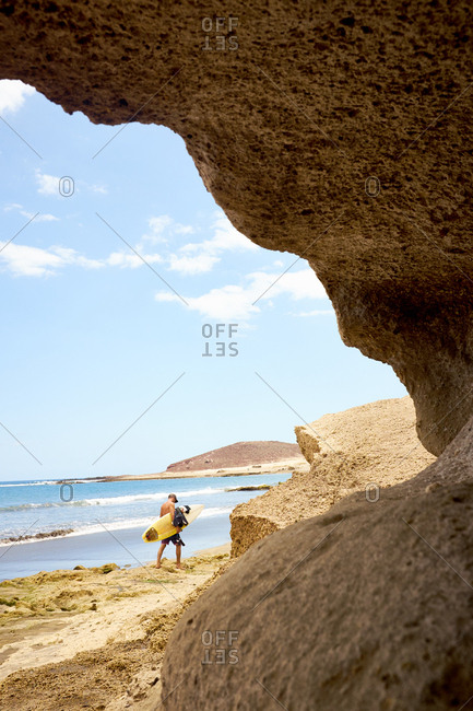 Tenerife, Spain - May 11, 2016: Male surfer on picturesque isolated beach, endless sunny sky hovering over blue water surface with small waves