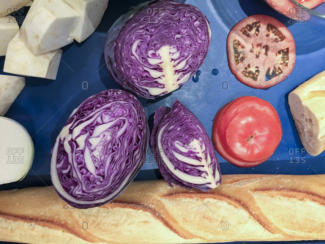 Overhead view of red cabbage, tomato and a baguette