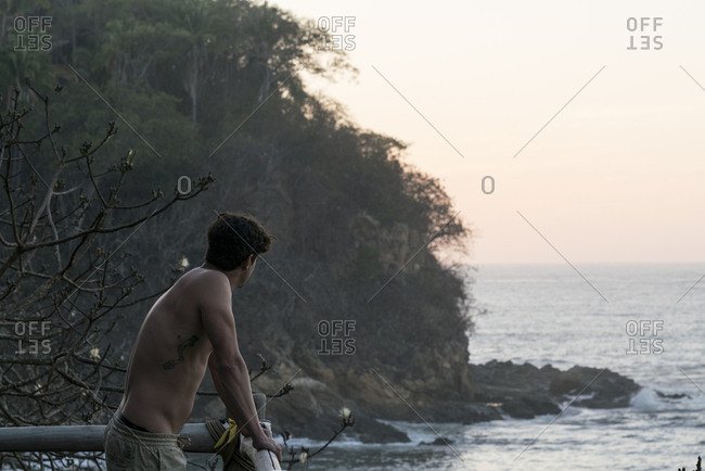 Man looking out to a Mexican beach at sunset