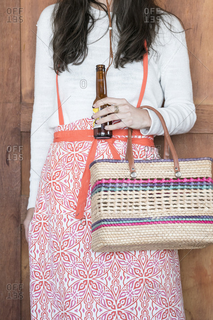 Woman holding wicker bag and beer