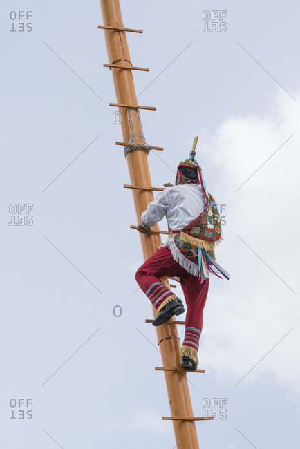 Man in colorful outfit climbing a ladder