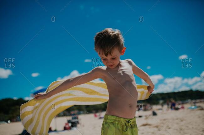 Boy holding towel in coastal breeze