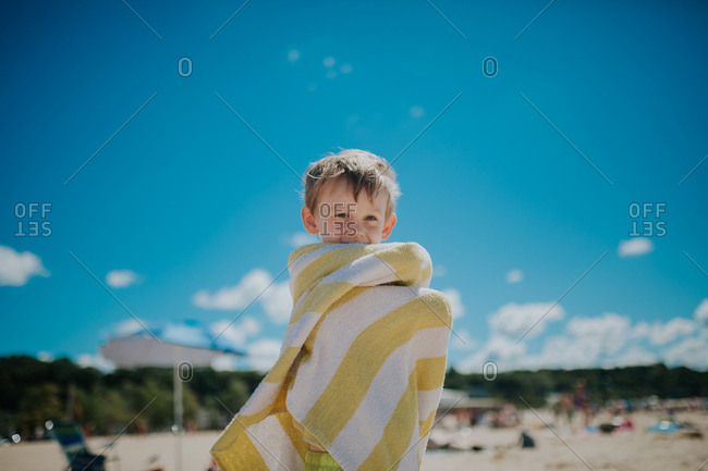 Boy wrapping himself in beach towel