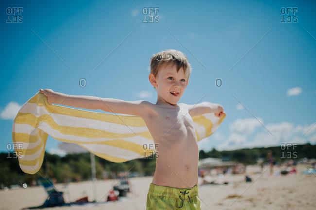 Boy holding towel in beach breeze