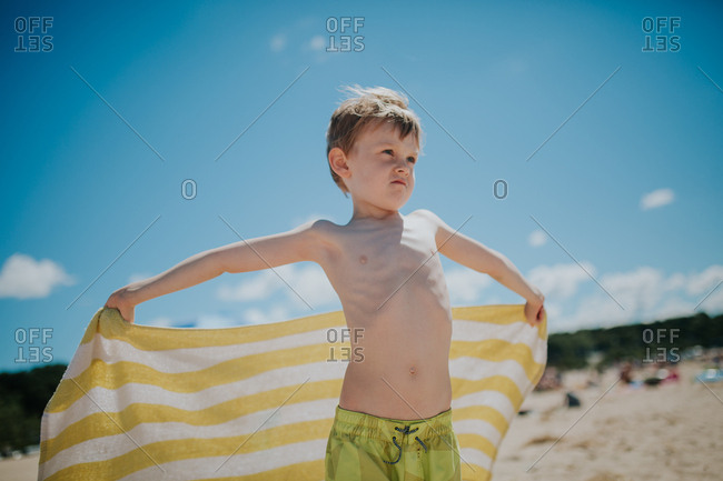 Boy making face holding up beach towel