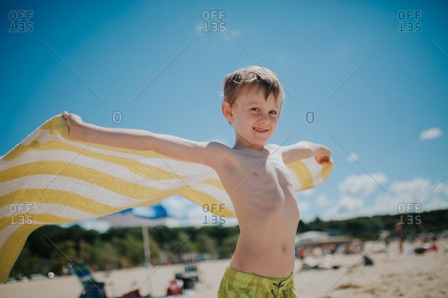 Boy holding a towel in beach breeze