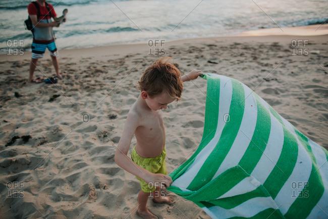 Boy holding a towel in beach wind