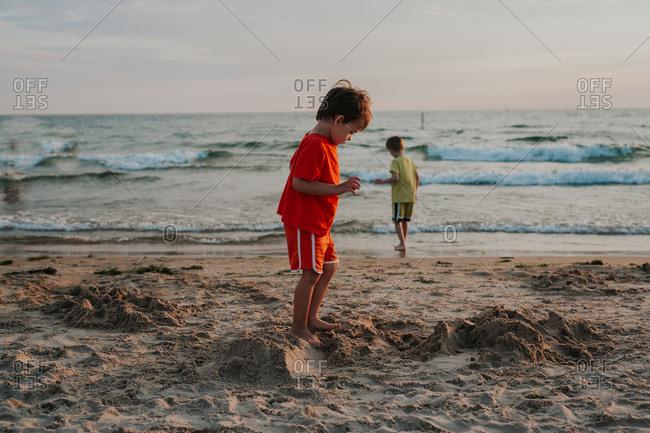 Boy staring at sand on beach