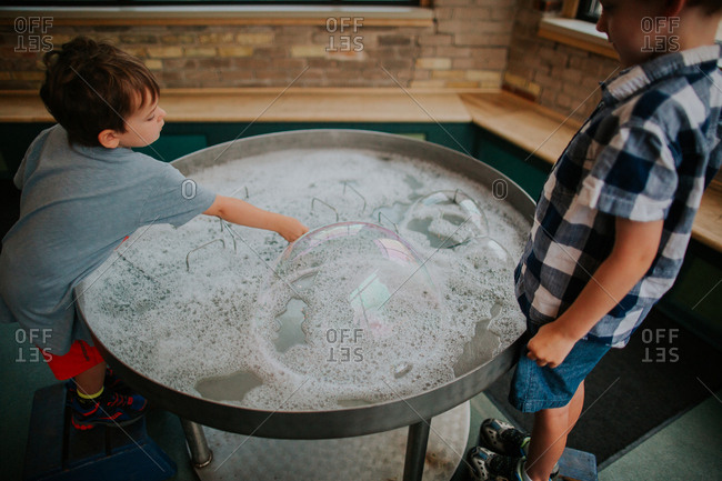 Boy touching soapy water with bubbles