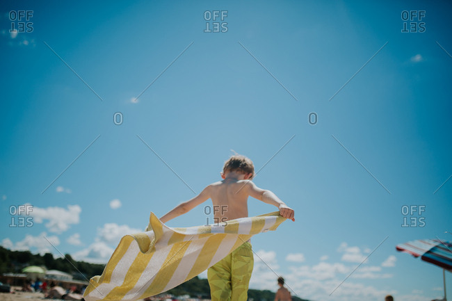 Boy holding beach towel in breeze