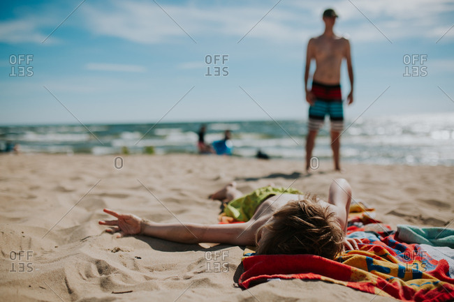 Boy sprawled on his beach towel