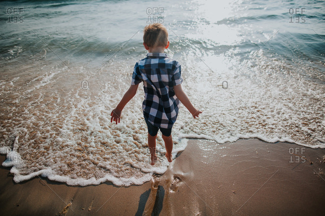 Boy standing the surf with bare feet