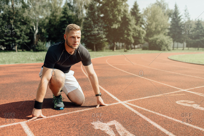 Focused male runner at starting position