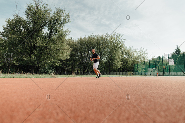 Ground level view of a runner training at a field and track course